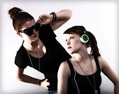 Two cool young women posing with sunglasses and headphones