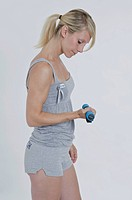 Young woman holding a small dumbbell in her right hand