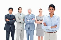 Multicultural business team with their arms folded with a woman smiling in foreground
