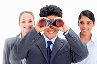 Close_up of a smiling businessman looking through binoculars with women behind him