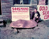 Historical photograph of a man posing with a large copper nugget. The sign behind the man reads: 5445 pound native copper nugget. Believed to be the l...