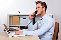 Happy business man with laptop computer in office making phone calls