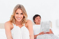 Woman at the bottom of the bed smiling as the man reads at the top of the bed