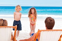 Children standing in front of their parents on the beach