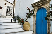 Door with carved stone surround and an old ceramic jar decorate a lane in Kythira town, Kythira, Greece