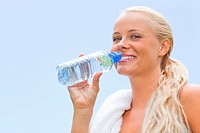 Smiling sportswoman about to drink some water