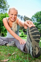 Smiling sportswoman doing stretches