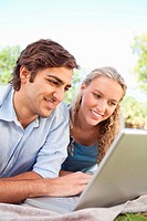 Smiling couple using their laptop on the lawn