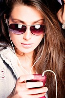 young woman listen music from cell phone with earphones wearing sunglasses, studio shot