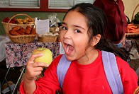 Young girl ready to bite into an apple at school site farmer´s market. The market is open 2 days a week from 4_6 p.m and is at an inner city primary s...