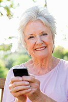 Woman smiling and looking ahead while using her phone