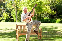 Man playing the guitar with a leg raised in front of a bench