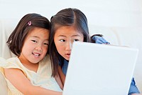 Two girls sitting on the couch while using a tablet