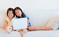 Two girls looking forward and smiling while holding a laptop on the couch