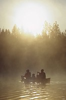 Family paddles canoe at early morning on Snake River, Wy. Mother, father, and two children with PFDs paddle in early morning mist, Grand Teton Nationa...