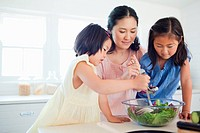 A mother and her daughters help to make a salad