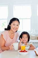 A mother and daughter smiling and sitting at the table to enjoy some food
