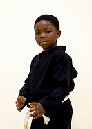 Portrait of a boy in martial arts gi and pose, white belt, dark gi, three quarter view pose. Hands are open up at his waist.