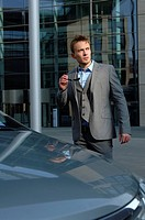Young businessman standing in front of the building of a bank, next to a car