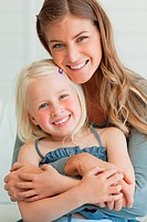 Close up of a mother and daughter smiling and embracing