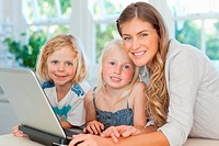 Mother and her kids at the laptop look forward and smile