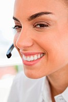 Close_up of a smiling tanned woman wearing headphone