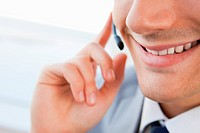 Close_up of a smiling man's mouth talking with a headset