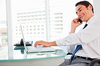 Smiling businessman calling while tapping his laptop