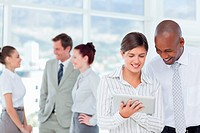 Smiling salespeople looking at tablet computer