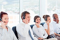 Smiling call center agent sitting among her colleagues