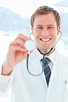 Smiling doctor examining with stethoscope