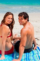 Portrait of a young smiling couple sitting on beach towel