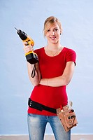 Young woman holding a drill