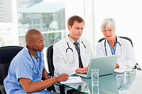 Doctors sitting in meeting room with a laptop