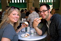 A couple eating beignets at Cafe Du Monde in the French Quarter of New Orleans, Louisiana.