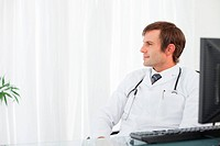 Serious doctor sitting at his desk while looking to his side