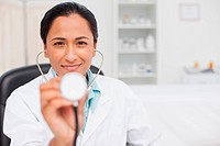 Smiling doctor holding her stethoscope while sitting in her office