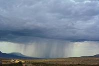 Cloud forms a large cumulonimbus formation with rainshaft over southwestern desert.