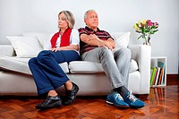 Full length of senior couple sitting on sofa after quarrel