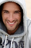 Man, early 30s, wearing a hooded sweater in bad weather at the beach, portrait