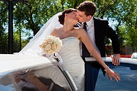 Passionate married couple kissing while standing in limo