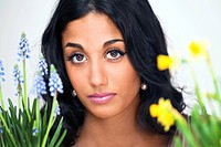 Face closeup of lovely young woman with flowering plants