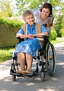 Senior woman in a wheelchair with her caregiver
