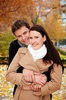 Happy smiling couple embracing in a fall park