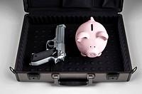 Piggy bank and a gun in a briefcase