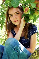 Smiling girl sitting in fruit tree