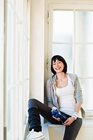 Smiling woman sitting in windowsill