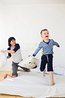 Mother and son having pillow fight