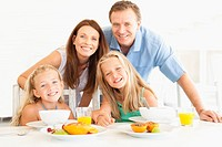 Family smiling at breakfast table
