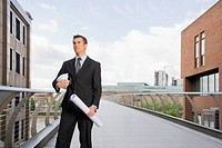 Businessman with blueprints on walkway